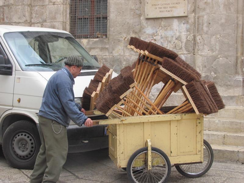 man carrying brooms