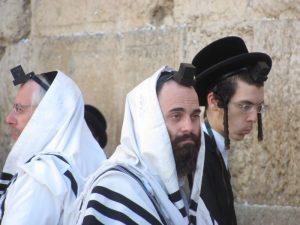 men praying at western wall